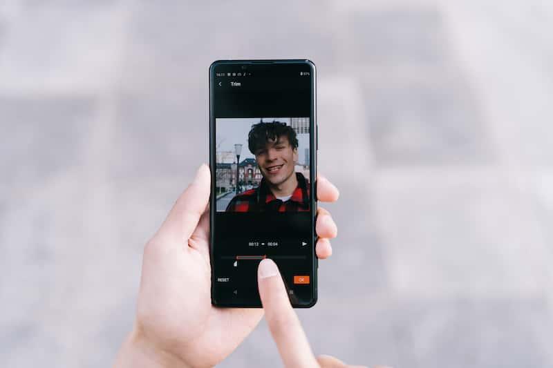 Situasjonsbilde av en person som bruker smarttelefonen til å redigere en video